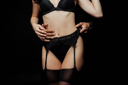 cropped view of man touching panties of sexy woman isolated on black