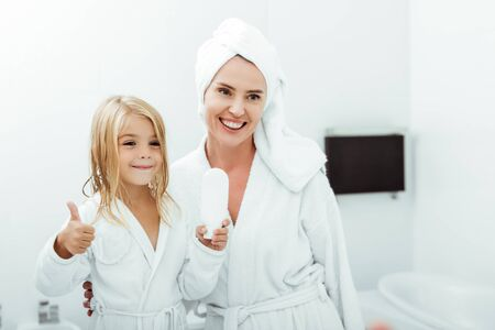 cheerful kid holding white bottle and showing thumb up near mother in towel and bathrobe Archivio Fotografico