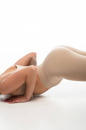 partial view of tattooed sexy blonde girl in beige leggings twerking on floor isolated on white Banque d'images