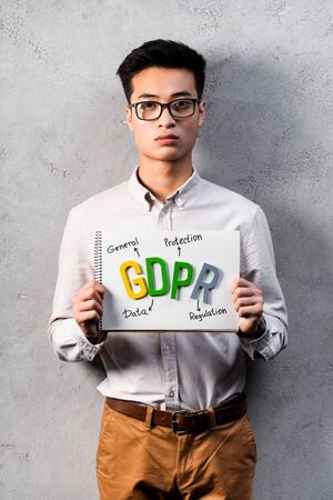 asian businessman holding paper with gdpr lettering and looking at camera