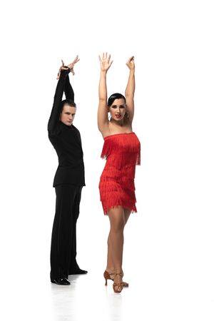 expressive couple of dancers looking at camera while performing tango with raised hands on white background Фото со стока