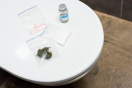 lsd, marijuana buds, cocaine and medical cannabis on toilet bowl