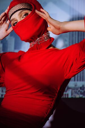 stylish woman in red dress and balaclava on city background