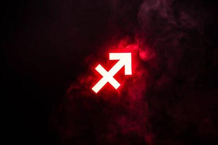 red illuminated Sagittarius zodiac sign with smoke on background Reklamní fotografie