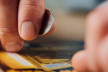 Nahaufnahme der Silbermünze in der Hand des Spielers in der Nähe des zerkratzten Lottoscheins