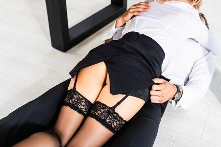Vista ritagliata della donna in calze sdraiata sull'uomo d'affari sul pavimento in ufficio