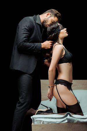 bearded man wearing blindfold on sexy woman in underwear isolated on black