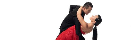 panoramic shot of elegant couple performing tango isolated on white Фото со стока