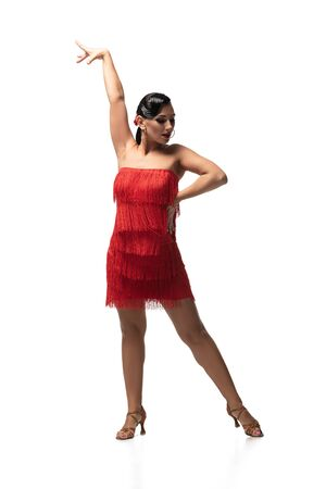 beautiful, passionate dancer in red dress with fringe performing tango on white background
