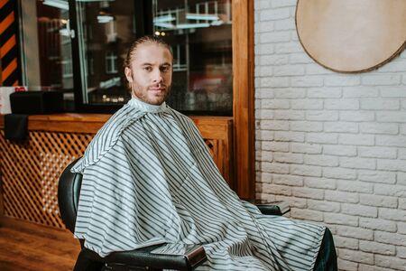handsome bearded man sitting in barbershop Reklamní fotografie