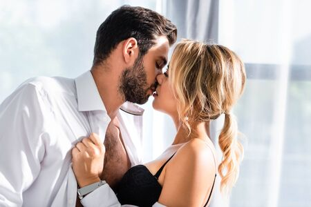 Side view of blonde woman kissing businessman in office