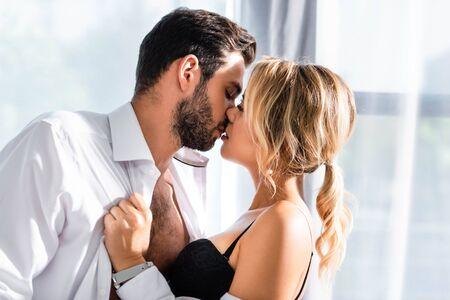 Vista laterale della donna bionda che bacia uomo d'affari in ufficio in