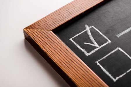 close up of chalk board with white tick on white Stock Photo