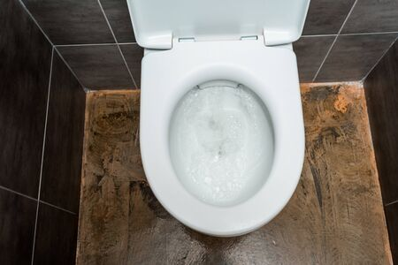 ceramic clean toilet bowl with flushing in modern restroom with grey tile