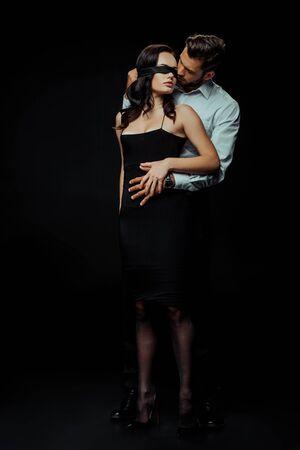bel homme regardant la femme aux yeux bandés sur le noir