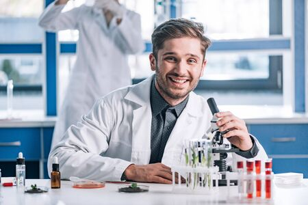 selective focus of happy biochemist near microscope and plants in test tubes