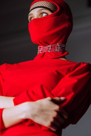 low angle view of stylish woman in red dress and balaclava isolated on grey