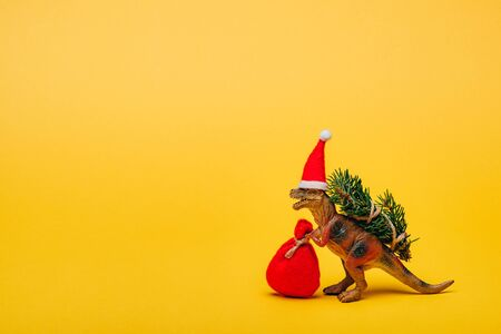 Toy dinosaur in santa hat with sack and fir on yellow background