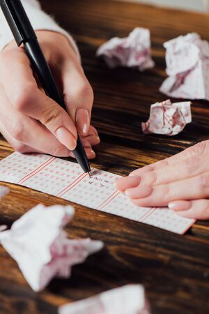 partial view of gambler marking numbers in lottery ticket near crumpled lottery cards on wooden table Standard-Bild