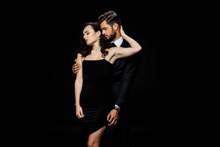 bearded man with closed eyes touching dress of girlfriend isolated on black Reklamní fotografie