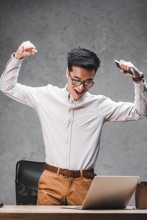 smiling asian seo manager showing yes gesture and looking at laptop