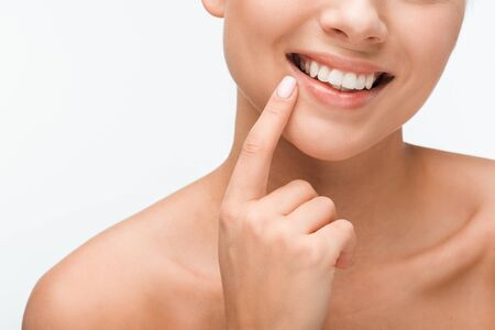 cropped view of happy woman pointing with finger at face isolated on white