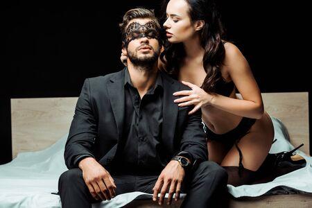 woman in underwear sitting near blindfolded man isolated on black Stockfoto