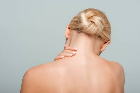 back view of naked woman touching neck isolated on grey