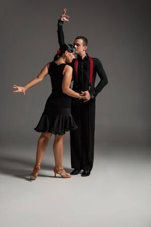two expressive dancers in black clothing performing tango on grey background