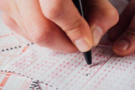 Vista de cerca de la mano del jugador marcando números en el billete de lotería con bolígrafo Foto de archivo