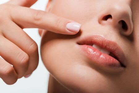 cropped view of woman pointing with finger at lips isolated on white  写真素材