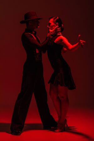 expressive couple of dancers in black clothing performing tango on dark background with red lighting
