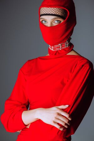 stylish woman in red dress and balaclava with crossed arms isolated on grey
