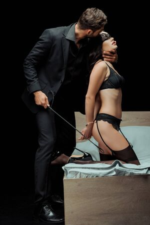 bearded man holding flogging whip and touching neck of seductive woman in underwear isolated on black