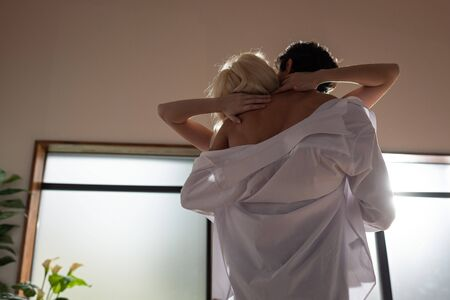 Back view of shirtless man embracing blonde woman in living room