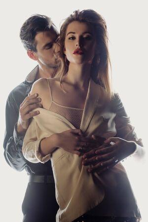 bell'uomo che abbraccia e bacia una donna attraente isolata su bianco