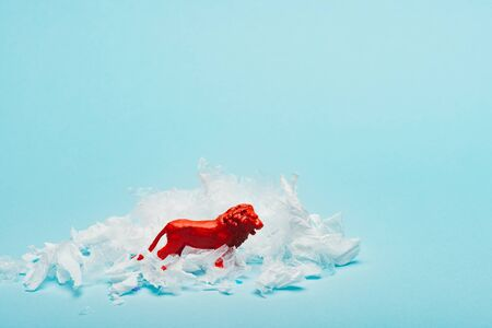 Red toy lion with plastic garbage on blue background, animal welfare concept