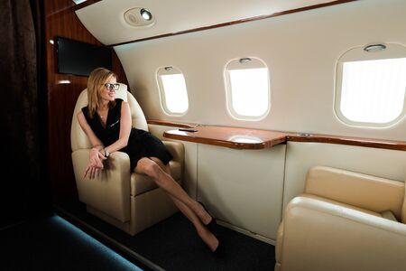 Alegre empresaria en gafas y vestido mirando a la ventana del avión en jet privado