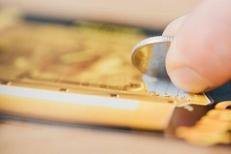 Vista cercana de la moneda de plata en la mano del jugador rascando el billete de lotería