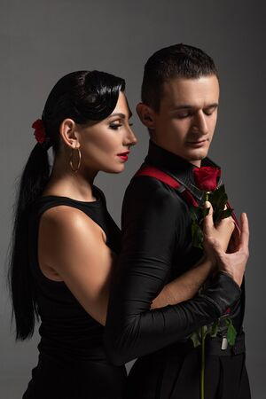 handsome tango dancer gifting red rose to attractive partner isolated on grey