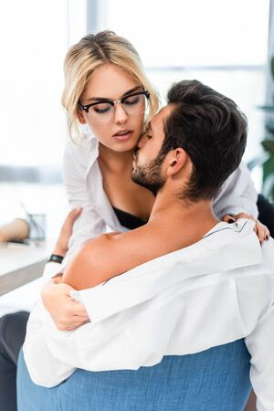 Sexy businesswoman taking off colleague shirt at office 版權商用圖片