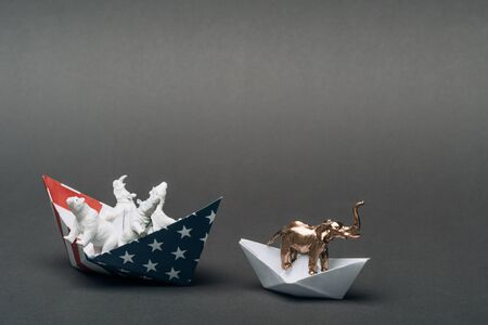 Toy elephant in paper boat and animals in boat from american flag on grey background, animal welfare concept Stock Photo