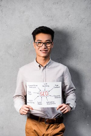 smiling asian seo manager holding paper with concept words of seo