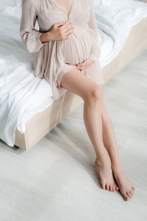 cropped view of pregnant girl in nightie touching belly while sitting on bed