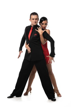 expressive, elegant dancers looking at camera while performing tango on white background Фото со стока