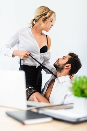Sexy businesswoman pulling tie of businessman in office