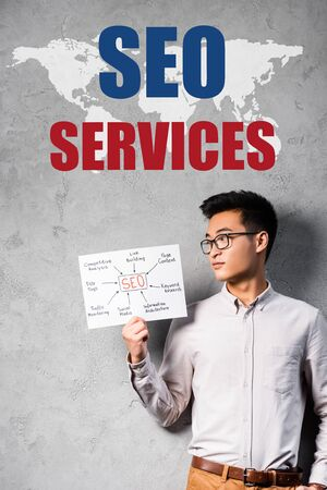 asian seo manager holding paper with concept words of seo and standing near seo services illustration