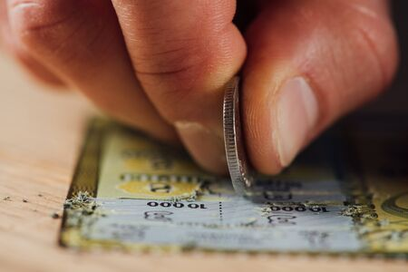 close up view of hand of gambler stretching lottery ticket