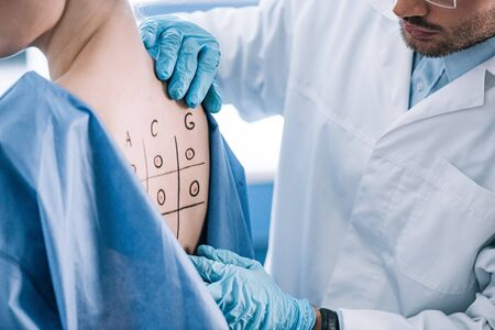 cropped view of allergist touching marked back with numbers and letters