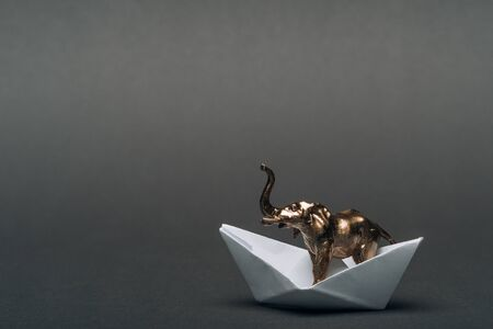 Golden toy elephant in paper boat on grey background, animal welfare concept Stock Photo